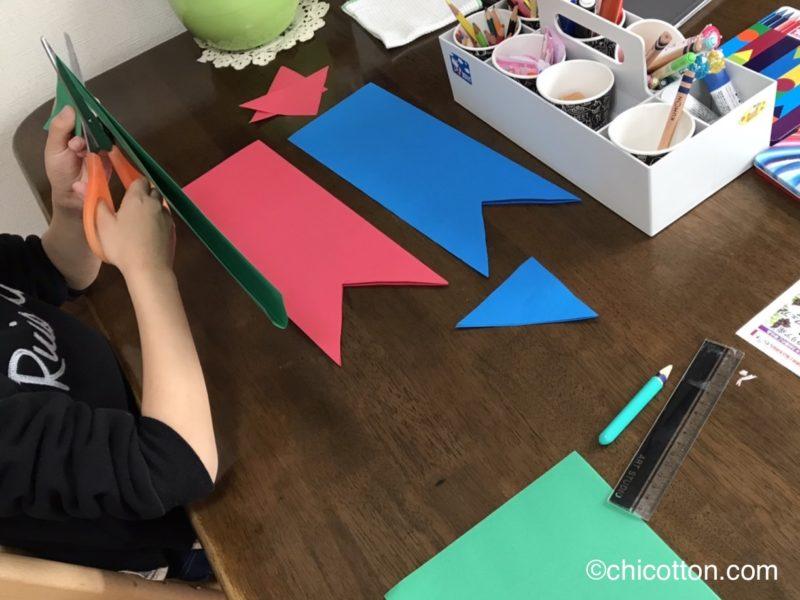 画用紙で作った鯉のぼりを作る子供