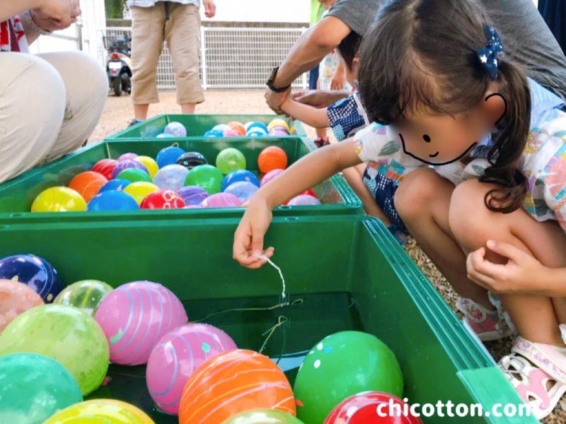 お祭りでヨーヨー釣りをする子ども